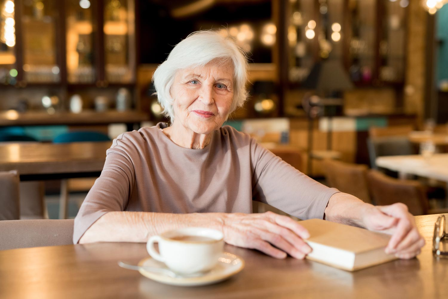 Senior Woman Smiling With Book And Coffee